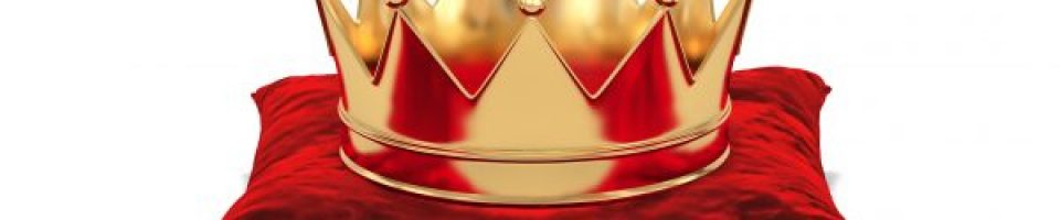 this is a photo of a gold crown on a red velvet pillow